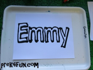 Use black glue to outline the name and set it aside to dry.